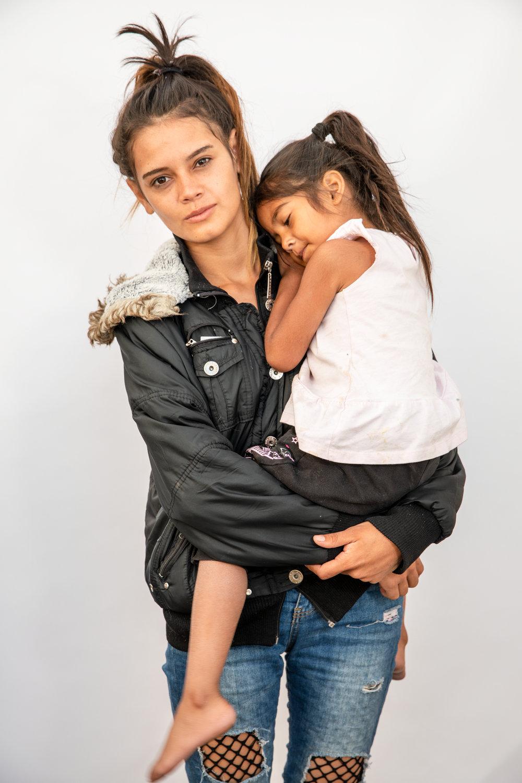"""""""Vengo huyendo porque mataron a mi mamá y a mi hermano. Entonces corro peligro yo también,"""" - Dijo Kenia Arias de 19 años y su hija Sury Belyini Ramos de 4 años, originarias de Tegucigalpa, Honduras, en Mexicali, México. Arias tuvo que dejar a su otra bebé de 6 meses en casa. """"Es muy duro dejar a la familia y sí, en verdad que duele mucho y uno hace hasta lo imposible para buscar el sueño americano, para buscar un futuro mejor, una mejor vida, porque allá en nuestro país ya no se puede ni vivir."""""""