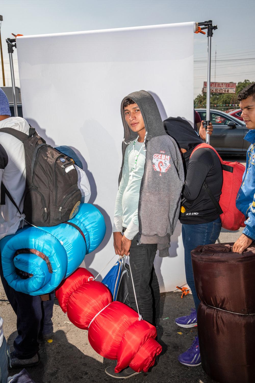 Maynor Alvarado de 19 años, originario de San Pedro Sula, Honduras, posa para una foto mientras espera abordar un trailer en las afueras de la Ciudad de México el 10 de Noviembre de 2018.