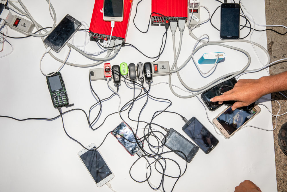 People charge their cell phones, as the migrant caravan, traveling from Central America, rests in Irapuato, Guanajuato, Mexico November 11, 2018. This caravan was made up of thousands of people and one of the biggest caravans to date. Migrant caravans have been happening for years, people from Central America travel together for safety.