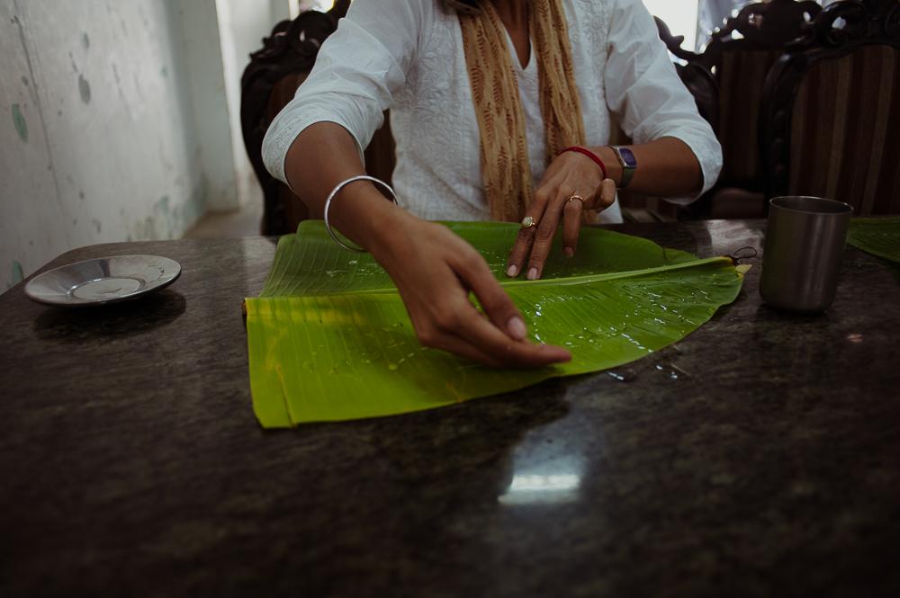 Aruna preparing a banana leaf for a meal.