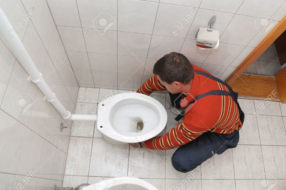 15832532-Plumber-replacing-broken-toilet-in-a-washroom-Stock-Photo-repair.jpg