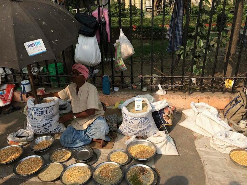 Vendedor ambulante de especias en la India, cobrando a través de PayTM