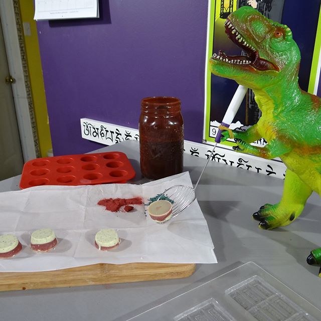 Hard at work for our events this weekend, Troy the T-Rex is posing here while he tempers and dips chocolate wth the help of Phoenix the Griffin and Frederick the Dragon lord. When he's not bellowing his version of Tuvan throat singing he likes whistling the theme song to Annie.... Sorry Robyn. Come see us @kootenayartisanfair in Nelson all weekend as well as @summerhillwine  this Saturday, @holisticmarketpsychicfair on Sunday and sample some of this amazing candy cane honey sweetened chocolate.  Stay tuned for more adventures in chocolating. #dairyfree #raw #rawfood #sexychocolate #alchemy #tarot #dinosaur #dragons #griffin #theobroma #rawchocolate #honey #silly #holidays