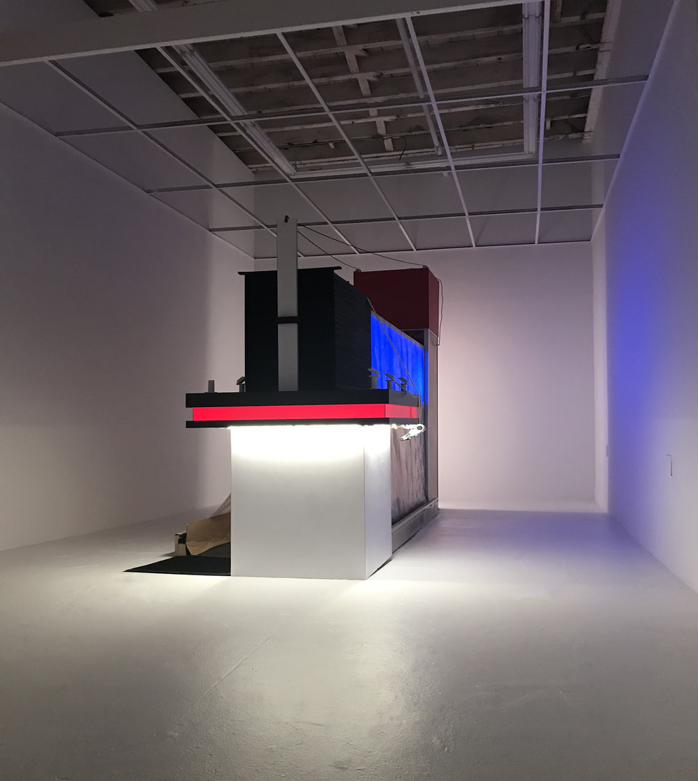 Jonathan Mildenberg  I.N.C.H. , 2018 wood, Formica, plexiglass, LED lights, ratchet straps, prefabricated cellphone security displays, carpet, foam, plastic tarp, rubber, tile, cardboard, steel, prefabricated light box, subwoofer, aluminum, self-adhesive vinyl, drywall, bed sheet, yoga mat, fabricated, neon light, mirror, porcelain tile, epoxy dimensions variable (JM6)