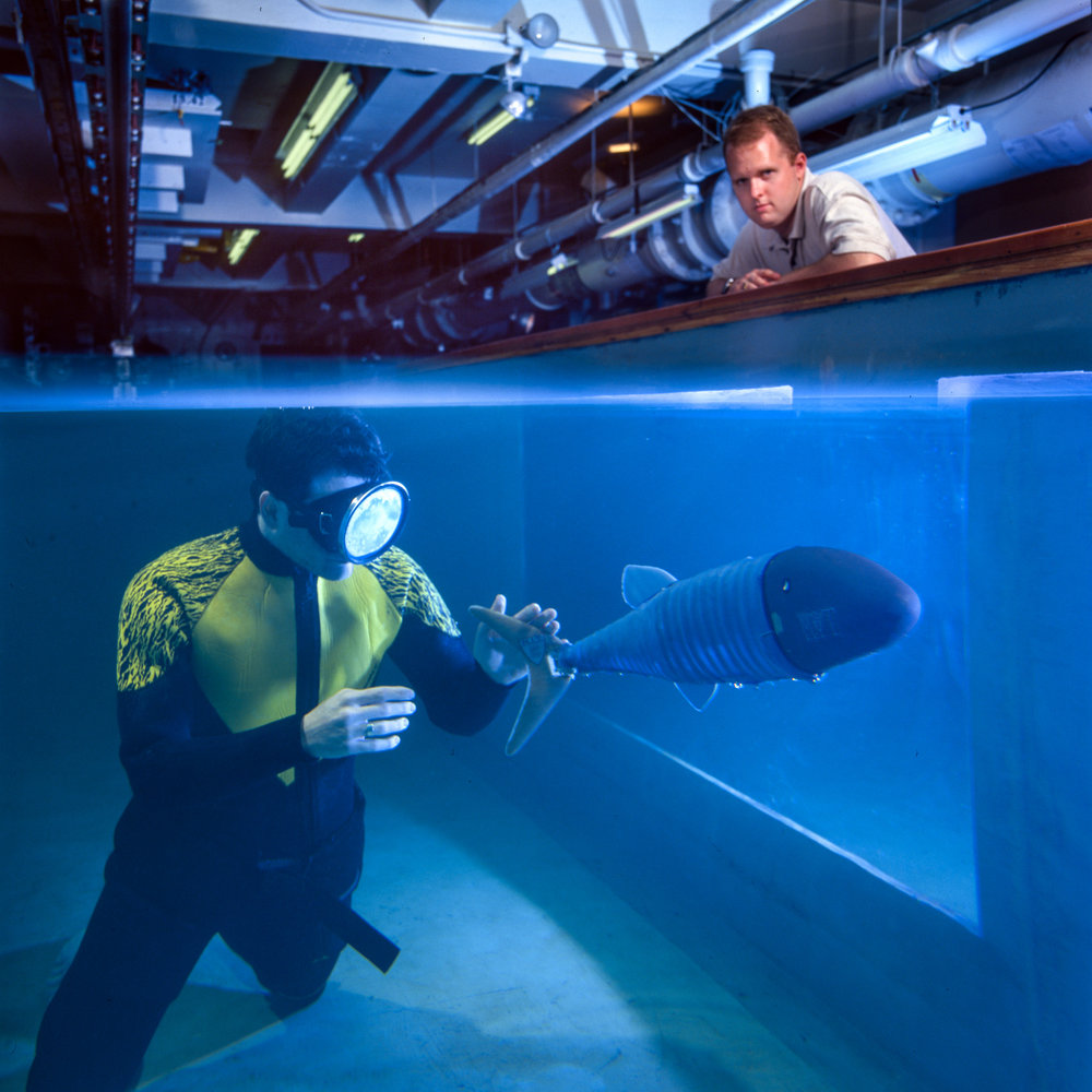 John Kumph (in water), a senior in mechanical engineering at MIT with a robot called RoboPike in MIT's Ocean Engineering Test Tank
