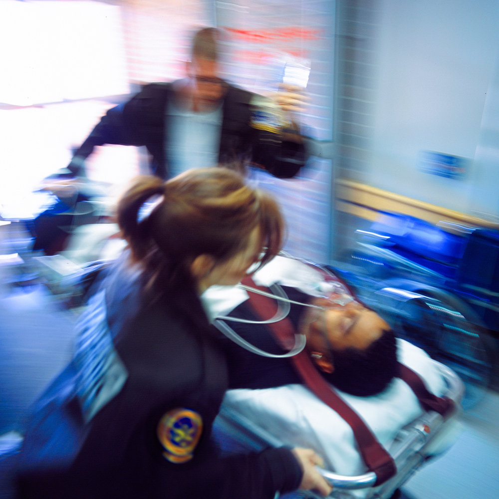 Paramedics rushing a patient in to an emergency department.