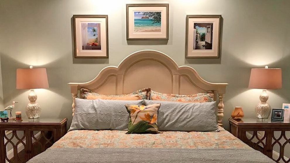 three of my hawaiian giclees adorning the wall above a bed.