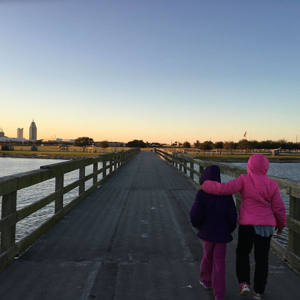 Precious's two little girls walking on a pier in Mobile Bay, in Alabama, during one of her history detective trips. They, along with her husband, have accompanied her on several of these research journeys.