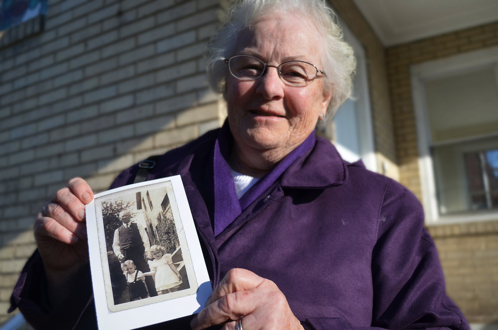 Sister Sheila holding a photograph featuring her grandfather, her brother, and herself in front of 3159 Ellers Street