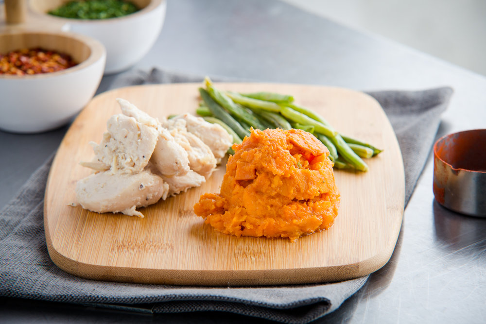 Shredded Chicken w/ Mashed Sweet Potato & Green Beans   Calories: 324  Protein: 37g  Carbohydrates: 30g  Fat: 3.4g  Sugar: 6.4g  Gluten Free  Ingredients: Chicken that is shredded with salt, pepper and garlic. Served with mashed sweet potatoes seasoned with agave. The green beans are steamed and seasoned lightly in salt.