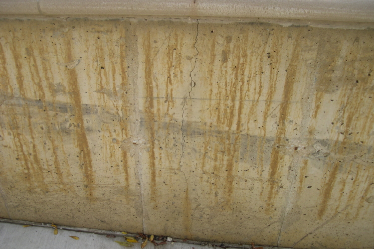 Discoloration Of Concrete Driveway Retaining Wall Before Installation Of Patterned Cement Overlay