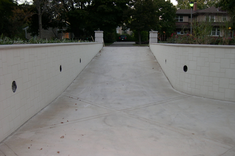 Both Sides Of Concrete Driveway Retaining Wall After Installation Of Patterned Cement Overlay