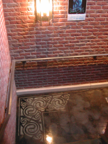 Black Acid-Stained Concrete Stairwell of Restaurant with Engraved Border