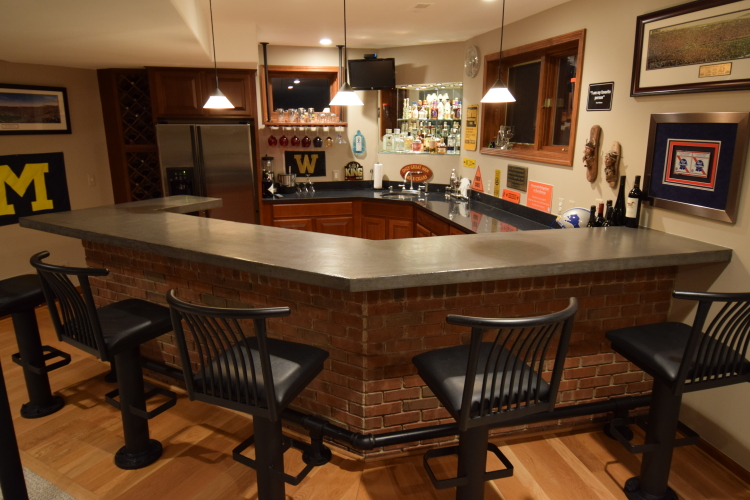 Gray Decorative Concrete Overlay of Wood Bar Countertop In Finished Basement After Applying Clear Epoxy Sealer And Matte Wax