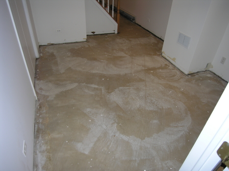 Finished Basement Concrete Floor Covered With Paint Spatter And Overspray Prior To Acid-Staining
