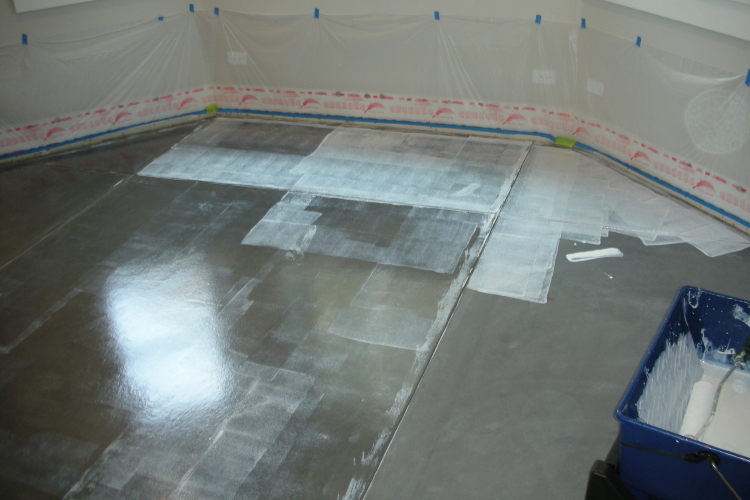 Water-Based Clear Epoxy Sealer Being Applied To Charcoal Gray Finished Basement Concrete Floor