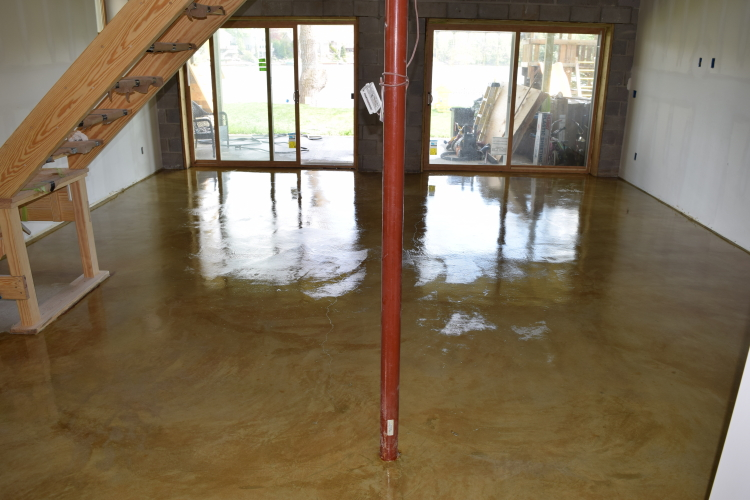 Yellow-Gold Acid-Stained Basement Concrete Floor With Clear Epoxy Sealer Looking Out Doorwall