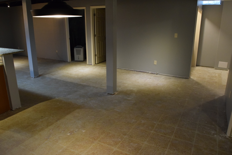 Finished Basement Concrete Floor With Yellow Tile Adhesive Before Grinding And Acid-Staining