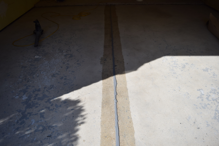 Old Garage Concrete Floor After Repairs And During Filling Of Control Joint