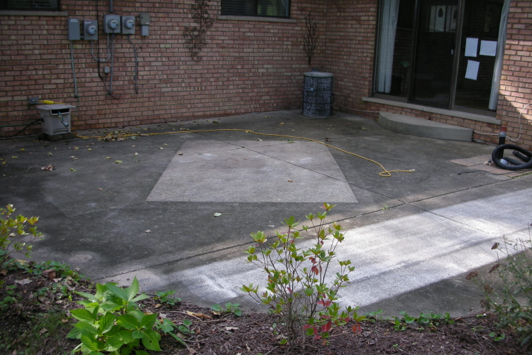 Weathered, Discolored Backyard Concrete Patio Before Cleaning And Installing Decorative Concrete Overlay