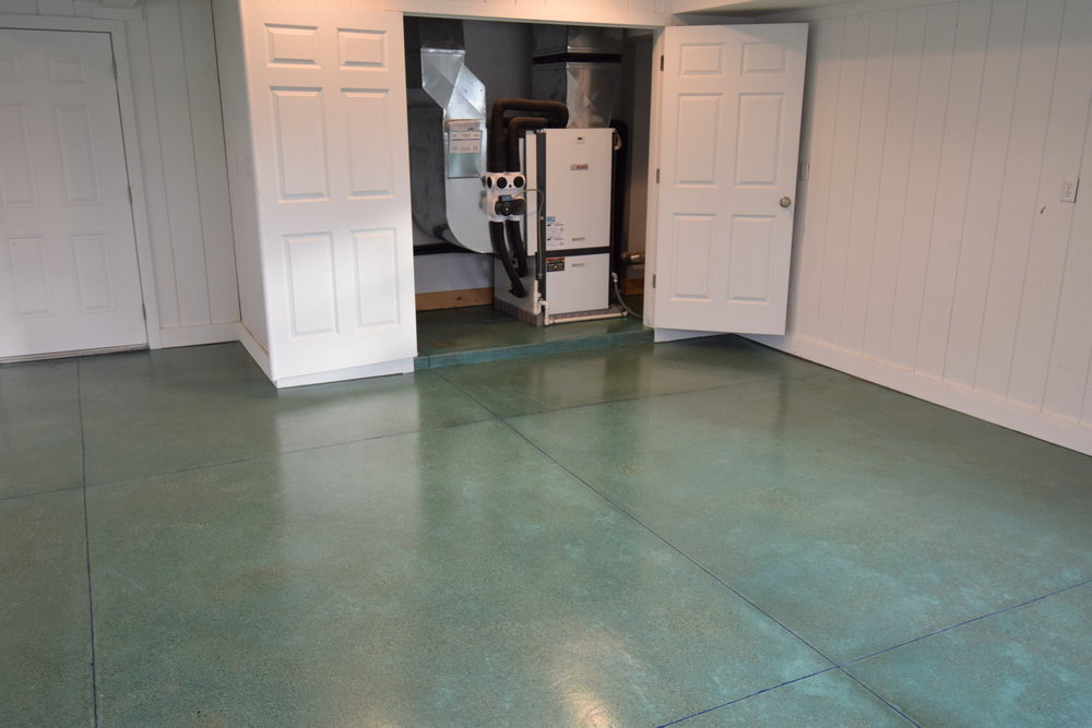 The saw-cut control joints in this two-car garage were filled with dark blue polyurea joint filler to accent the blue-green acid stain and keep the joints from filling with salt and snow in the winter and joint edges from spalling due to vehicle tire pressure.