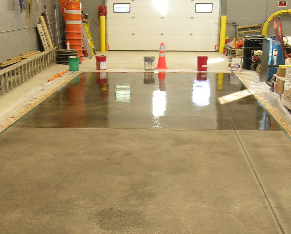 "This warehouse concrete floor ""bay"" was acid-stained to protect it from oil spills and stains during equipment maintenance. Above, a clear polyurea sealer is being applied to deepen the color of the stain and add a hard, durable, protective glossy film."