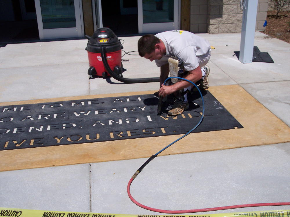 Acid-Stained Concrete Church Entryway During Engraving Of Bible Verse Using Plastic Template