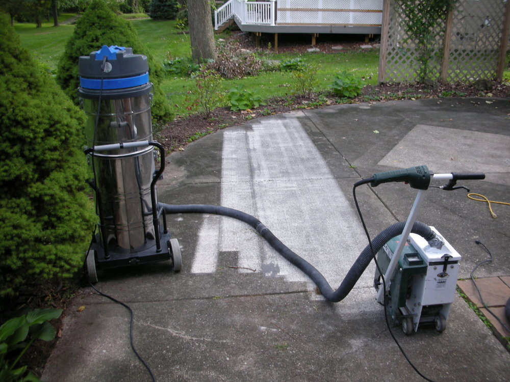 Shot-blasting was required to clean this backyard concrete patio, before resurfacing with a cement overlay, because of the rough texture and longstanding dirt and discoloration.