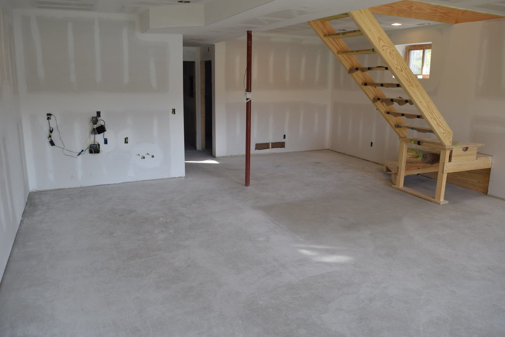 This new basement concrete floor might looks to be in pretty clean condition.  But notice the rectangular area under the stairs. That is where sheets of drywall lay prior to installation.  That spot shows how much work really needs to be done before acid-staining this floor.