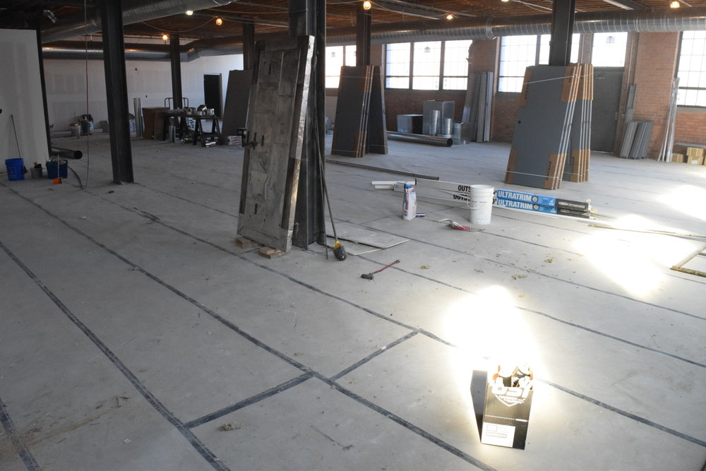 The owner of this new commercial concrete floor protected it with Ram Board until it was time for us to install the decorative finish.  Ram Board consists of heavy duty fiber paper, rolled out and taped at the seams.