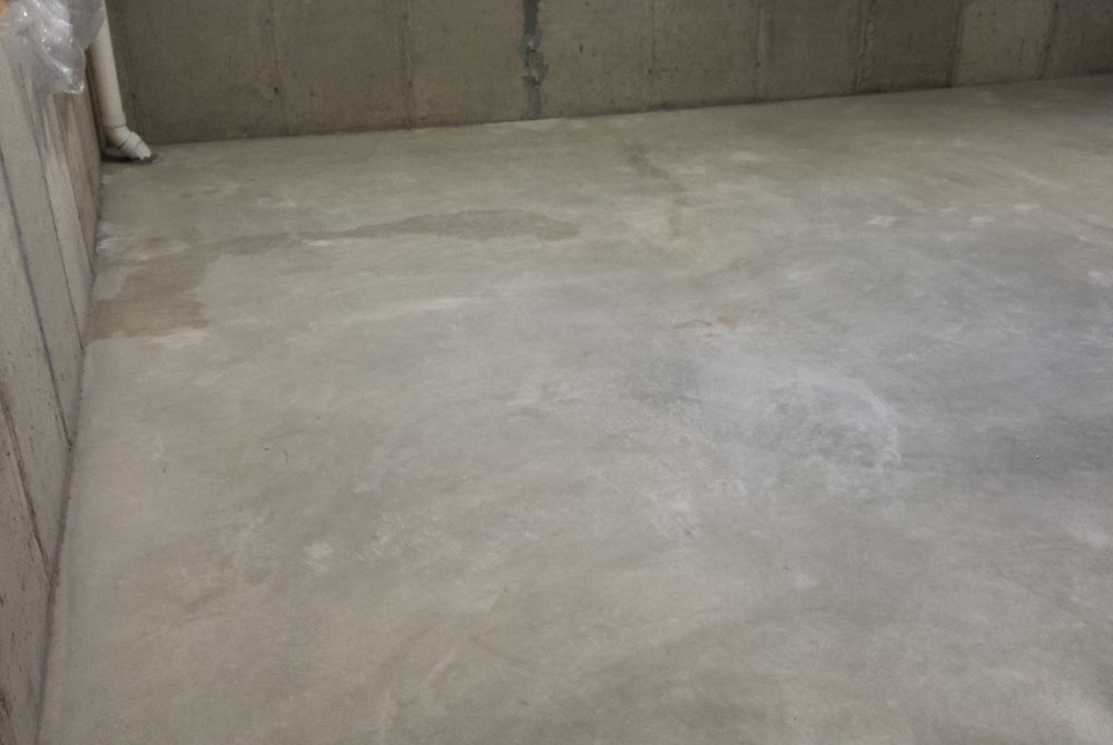 The wet spot on this basement concrete floor was caused by a garbage bag of wet material sitting there for months.  Without testing, it is impossible to tell how bad this spot really is and how long it might take to dry out.