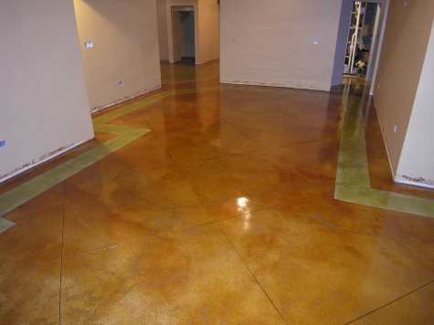 """This acid-stained finished basement concrete floor had 3.5' diagonal Spanish tiles cut in the interior and an 18"""" border along the walls done in a contrasting color. Notice the distinct color separation on both sides of the border."""