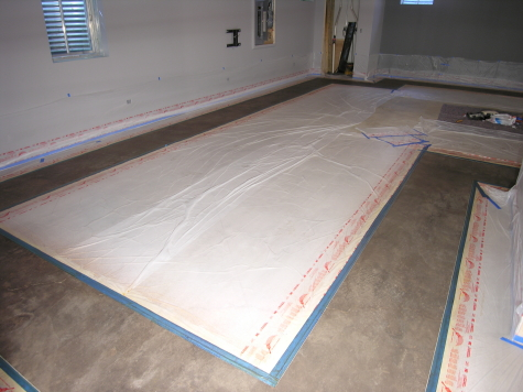 Gray acid-stained basement concrete floor masked off with tape and plastic to protect it while acid-staining a dark black border