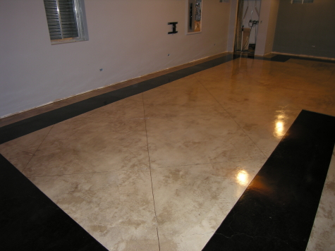 Gray acid-stained basement concrete floor with interior diagonal tiles and acid-stained dark black border