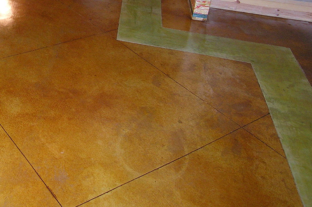 Here is a finished basement acid-stained concrete flooring project that turned out great except for one small area, where a wet hose sat overnight.  This color discrepancy was small enough that we were able to make it disappear through faux finishing.