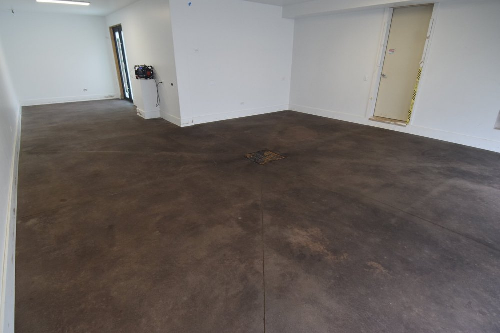 Garage Concrete Floor After Applying Black Acid Stain, Allowing 12 Hours For Reaction, And Rinsing