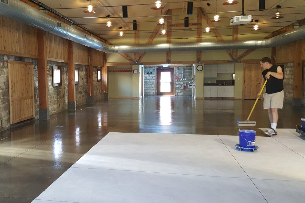 Museum Concrete Floor Being Coated With Clear Polyurea Sealer After Diamond Grinding