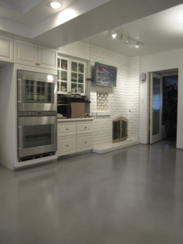 "Gray cement ""warehouse"" look flooring in a kitchen.  On the ground floor of a home with a basement, a self-leveling overlay is the only way to achieve this look."