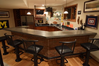 A matte, gray, concrete countertop bar in a finished basement that was created using a self-leveling overlay from the Bostik Company.