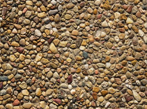 """A closeup photo of properly sealed exposed aggregate concrete illustrating the color variation in stone, and """"wet look"""" from the protective sealer."""