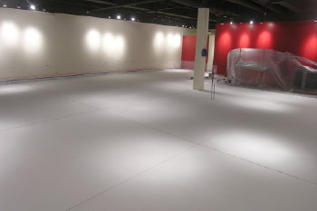 "Before we ground the concrete clean, and resurfaced it with this white cement overlay, this existing retail store floor in Buffalo Grove, Illinois, was covered with 1/4"" of yellow carpet glue and black ""cutback"" tile adhesive."