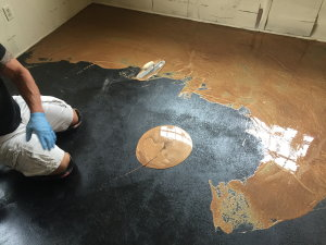 Metallic epoxy installations, like this one, usually start with black primer to increase the coating's contrast with the floor, followed by a layer of thick, colored epoxy spread with a trowel.  These coatings completely obscure the concrete beneath.