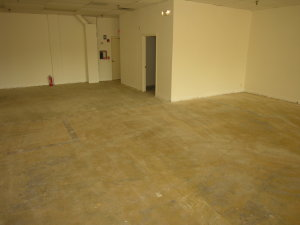 """The concrete floor in this retail store space is completely covered with a 1/8""""-thick layer of yellow carpet glue. Carpet glue on residential concrete is applied much more sparingly, often just in rows or in isolated areas."""