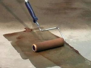 Here, water-based acrylic concrete stain is being applied, instead of acid stain, over a poorly prepared concrete floor in the hopes of covering up imperfections. Water-based stains are a bad choice, because they leave pattern application marks and don't look natural.