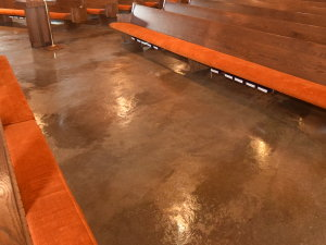 """On the above acid-stained concrete floor, you can see three parallel """"bands"""" of coloring that are a slight shade darker brown than the rest of the floor. This is due to shadowing left behind from carpet glue stripper."""