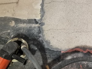 There was so much material on the surface of this concrete, including paint, glue, and previously applied cement overlays, that it had to be ground off, leaving exposed aggregate (upper right corner of photo).