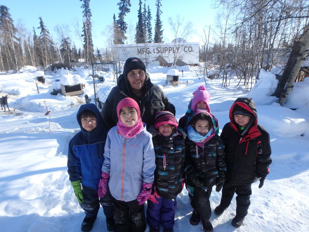 Minto School students with Musher Lloyd Charlie at his kennel.