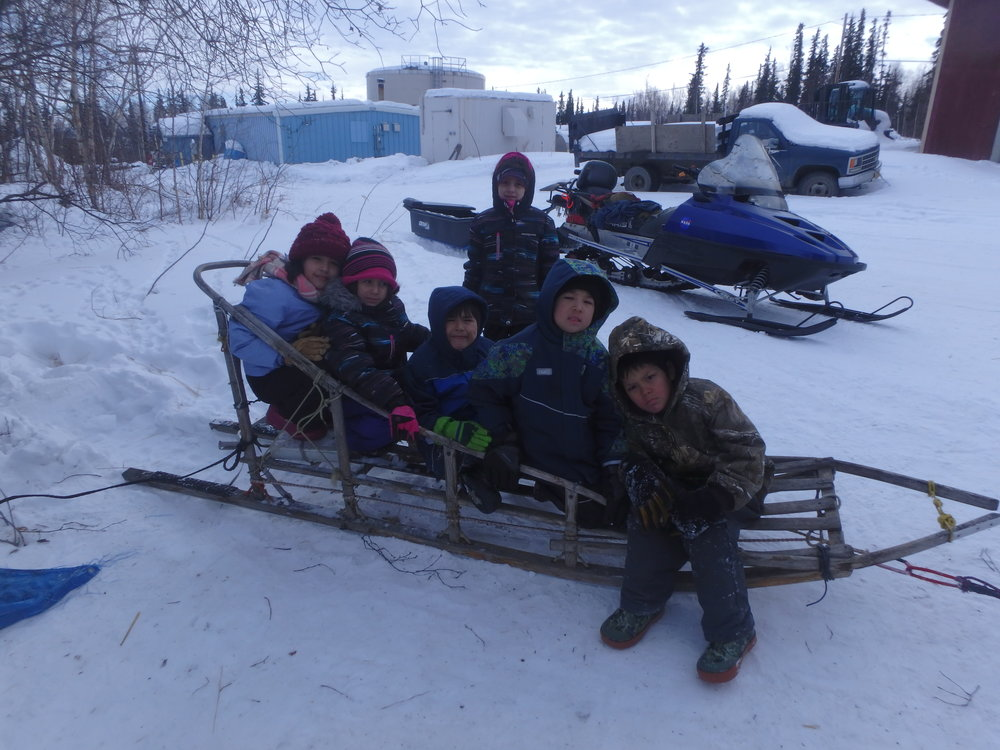 Minto School students sitting in Lloyd Charlie's sled.