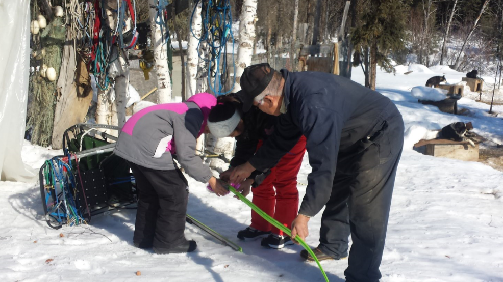 Allakaket School students learn from Musher Steven Bergman how to change sled runner.