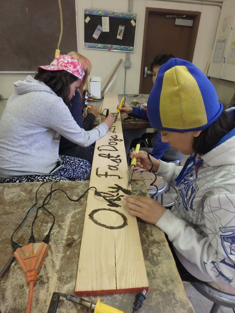 Minto School students finish burn letters into kennel sign.
